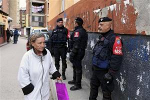 A woman passes by Italian Carabinieri, who are members of the NATO Kosovo Force, in the northern part of the ethnically-divided town of Mitrovica