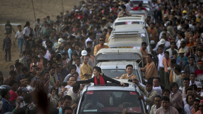 Opposition leader Aung San Suu Kyi reaches for supporters as she leaves after a public meeting close to Letpadaung mine in Monywa, northwestern Myanmar, Friday, Nov. 30, 2012. Suu Kyi is urging a negotiated resolution to protests over a military-backed copper mine in northwestern Myanmar after the government's biggest crackdown on demonstrators since reformist President Thein Sein took office last year. (AP Photo/Gemunu Amarasinghe)