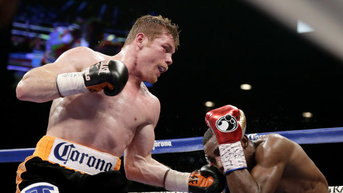 Canelo Alvarez, left, of Mexico, hits Erislandy Lara, of Cuba, during their super welterweight fight, Saturday, July 12, 2014, in Las Vegas