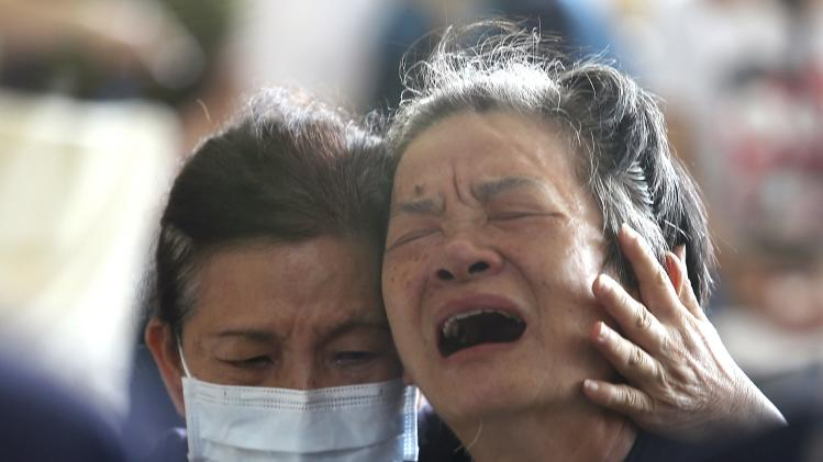 Relatives of the victims cry after an explosion in Kaohsiung, southern Taiwan