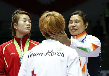 India's bronze medallist Laishram Sarita Devi reacts during the medal ceremony for the women's light (57-60kg) boxing competition at the Seonhak Gymnasium during the 2014 Asian Games in Incheon
