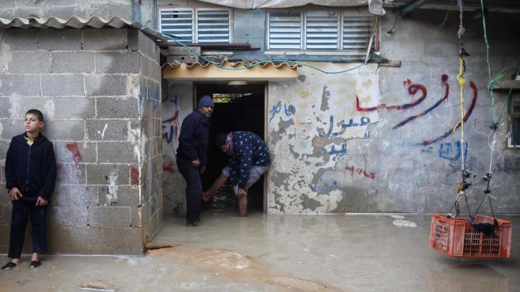 Palestinians stand at their house that is flooded on a stormy day in Rafah