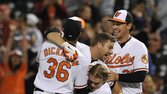 Baltimore Orioles Chris Davis, center, is picked up by teammates Nate McLouth, right, and Chris Dickerson after driving in the game winning run against the Boston Red Sox in the 13th inning of a baseball game Thursday, June 13, 2013 in Baltimore. The Orioles won 5-4.(AP Photo/Gail Burton)