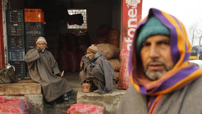 Kashmiri vegetable vendors sip tea as they wait for customers on a cold and foggy morning in Srinagar, in India, Thursday, Dec. 25, 2014. Cold wave tightened its grip on the Kashmir valley as it continues to reel under intense cold wave for the past few days with widespread snowfall in the hilly areas.(AP Photo/Mukhtar Khan)