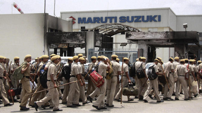 In this Saturday, July 21, 2012 photo, Indian police officers enter the Maruti Suzuki factory in Manesar, near New Delhi, India.  Shares of India's top car maker Maruti Suzuki have plunged after the company said it would impose an indefinite lockout at a factory consumed by a deadly labor dispute last week.  Investors bracing for a weeks long closure drove the stock down over 5.6 percent Monday.(AP Photo) INDIA OUT