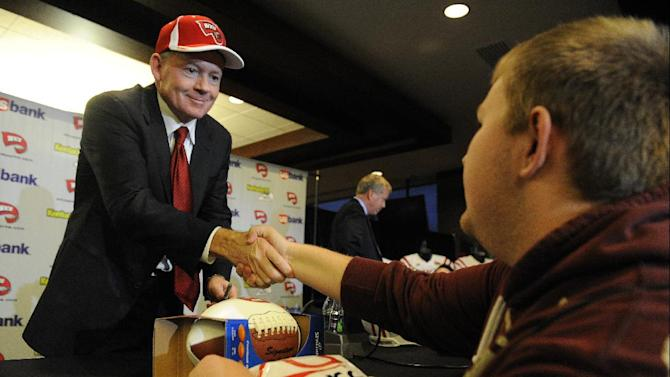 "New Western Kentucky head coach Bobby Petrino, left, shakes hands with student Jared Willis at an NCAA college football news conference, Monday, Dec. 10, 2012, in Bowling Green, Ky. The 51-year-old was fired by Arkansas in April for a ""pattern of misleading"" behavior following an accident in which the coach was injured while riding a motorcycle with his mistress as a passenger but now wants to make the most of his second chance. (AP Photo/The Daily News, Joe Imel)"