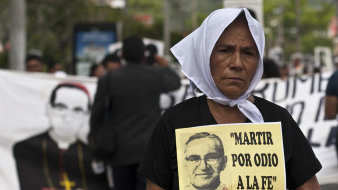 "A woman carries a portrait of slain Roman Catholic Archbishop Oscar Romero that reads in Spanish: ""Martyred by faith haters,"" during a protest by the relatives of people who disappeared in the nation's civil war in San Salvador, El Salvador, Thursday, May 21, 2015. The assassination came in the opening days of the Salvadoran civil war, one of the last major conflicts of the Cold War pitting leftist guerrillas against a U.S.-backed military junta and subsequent governments. (AP Photo/Salvador Melendez)"