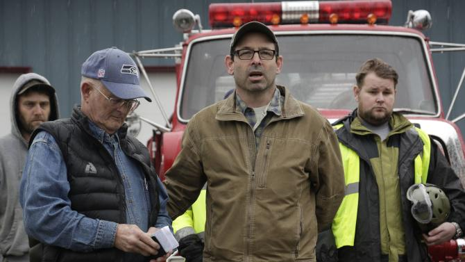 Darrington Mayor Rankin and Pastor De Luca lead workers and community members in prayer and a moment of silence marking the one-week anniversary of the Oso landslide at the fire station in Darrington, Washington