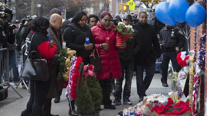 Emerald Garner, daughter of Eric Garner, center left, visits a makeshift memorial, Monday, Dec. 22, 2014, near the site where New York Police Department officers Rafael Ramos and Wenjian Liu were murdered in the Brooklyn borough of New York. Police say Ismaaiyl Brinsley ambushed the two officers in their patrol car in broad daylight Saturday, fatally shooting them before killing himself inside a subway station. (AP Photo/Seth Wenig)