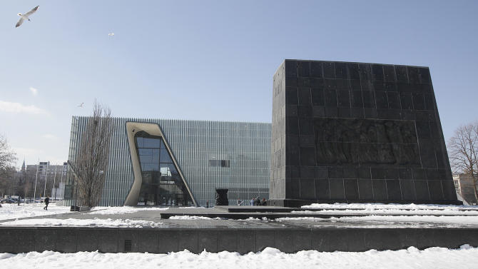 This Monday, April 8, 2013 photo shows the Museum of the History of Polish Jews, an ambitious new institution that is opening amid celebrations next week marking the 70th anniversary of the Warsaw Ghetto Uprising. At right is a monument honoring the fighters of the uprising. The revolt gave the world an enduring symbol of defiance against impossible odds, but in a Poland still adjusting to its post-Cold War freedoms, the memory of the Holocaust still engenders controversy in some quarters. The museum that is opening in the ruins of the Jews' prison of misery and death does not shy away from Poland's own history of anti-Semitism a sign, many say, that the country is maturing and riding a wave of confidence-building economic growth. (AP Photo/Czarek Sokolowski)