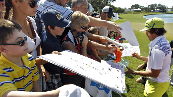 Rickie Folwer, right, signs autographs after completing a practice round for The Players Championship golf tournament Wednesday, May 9, 2012, at Sawgrass in Ponte Vedra Beach, Fla. (AP Photo/Chris O'Meara)