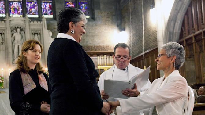 In this photo provided by Outserve-SLDN, Brenda Sue Fulton, center left, and Penelope Gnesin, hold hands while exchanging wedding vows at the U.S. Military Academy at West Point, N.Y.  Saturday, Dec. 1, 2012. Their ceremony marks the first time a same sex couple had their wedding in the Cadet Chapel, the landmark gothic church that is a center for spiritual life at the Academy. The chaplain and woman at left are unidentified. (AP Photo/Outserve-SLDN, Jeff Sheng)