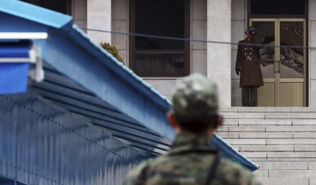 North Korean soldier looks south through a pair of field glasses as a South Korean soldier stands guard at truce village of Panmunjom in demilitarised zone dividing two Koreas, in Paju