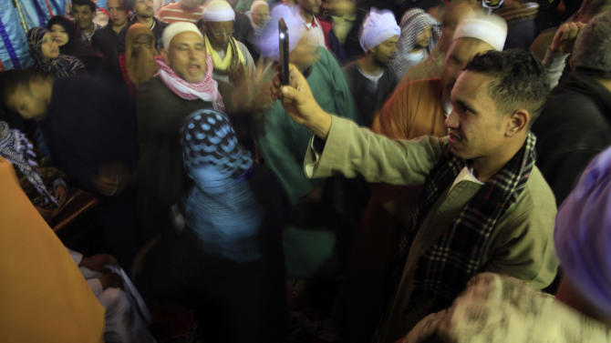 A man records a video as Sufi Muslims practice ritualized Zikr (invocation) celebrating Moulid Al-Hussein, the birthday of Prophet Mohammad's grandson Hussein, outside the Al-Hussein mosque in old Cairo