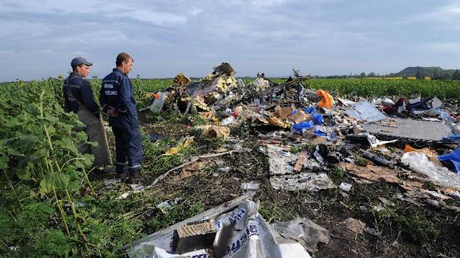 Employees of the Ukrainian State Emergency Service look at the wreckage of Malaysia Airlines flight MH17 in rebel-held east Ukraine, on July 19, 2014