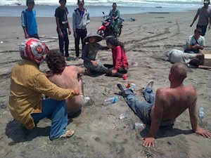 A group of asylum-seekers sit on the beach on September…