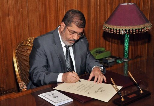 A handout picture released by Egyptian Presidency shows Egyptian President Mohamed Morsi at his office in the presidential palace in Cairo on December 26, 2012, as he signs into law a new constitution. Egypt's state prosecutor ordered on Tuesday an investigation into a claim that popular satirical show host Bassem Yousef insulted Morsi, a judicial source said