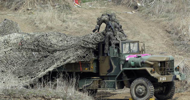 South Korean soldiers place a camouflage net over their military vehicle during a military exercise near the border village of Panmunjom in Paju, north of Seoul, South Korea, Thursday, April 4, 2013.