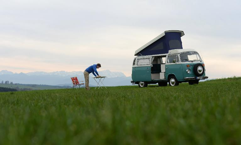 Volkswagen Kombi owner Wanja Fuhrmann sets up a camping table next to his Volkswagen T2 camper van built in 1975 near Landsberg, southern Germany, on November 1, 2013