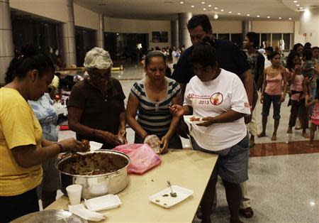 People receive food while camping out at a shelter after storms hit Acapulco