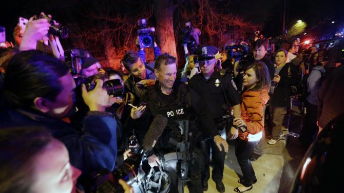 A gathering of people including the media gather around a police officer as he leaves the scene after the arrest of a suspect of the Boston Marathon bombings in Watertown, Mass., Friday, April 19, 2013. Two suspects in the Boston Marathon bombing killed an MIT police officer, injured a transit officer in a firefight and threw explosive devices at police during their getaway attempt. (AP Photo/Matt Rourke)