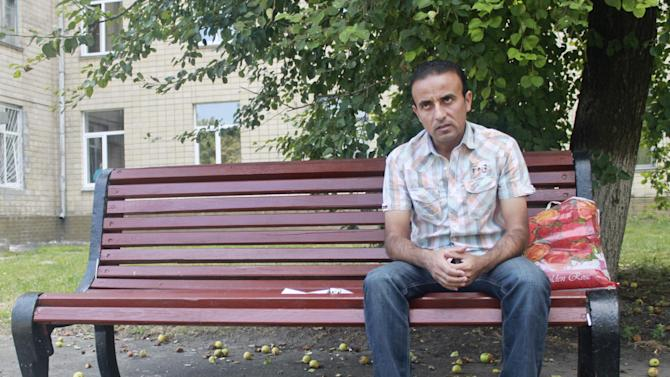 In this photo taken on Aug. 19, 2013. Hesham Abu Hmeid, a Palestinian asylum seeker, speaks to The Associated Press during an interview in Kiev, Ukraine. The United Nations refugee agency says this ex-Soviet republic is unsafe for many asylum seekers and the global watchdog Amnesty International has accused Ukraine and several other former Soviet states of running an illegal rendition program, unlawfully sending back asylum seekers to home countries where are likely to face torture and prosecution. (AP Photo/Maria Danilova)