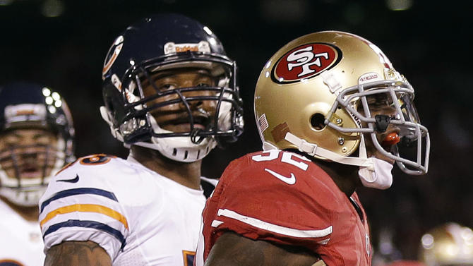 San Francisco 49ers running back Kendall Hunter (32) celebrates after scoring on a 14-yard touchdown run in front of Chicago Bears' Nick Roach (53) during the second quarter of an NFL football game in San Francisco, Monday, Nov. 19, 2012.  (AP Photo/Marcio Jose Sanchez)