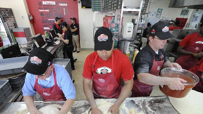 Papa John's employees David Noel, left, Jimmy Sosa, middle and Dan Krug prepare pizzas inside the New Hyde Park restaurant, the 4000th Papa John's store on Friday Sept. 14, 2012, in New Hyde Park, N.Y. A grand opening celebration took place. (Photo by Kathy Kmonicek/Invision for Papa John's/AP Images)