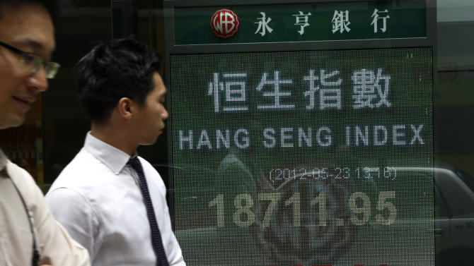 People walk past a screen displaying stock index outside a local bank in Hong Kong Wednesday, May 23, 2012. A report that Greece is considering preparations to leave the euro common currency sent Asian stock markets lower Wednesday. Hong Kong's Hang Seng fell 1.7 percent to 18,721.37 in the mid-day close. (AP Photo/Vincent Yu)