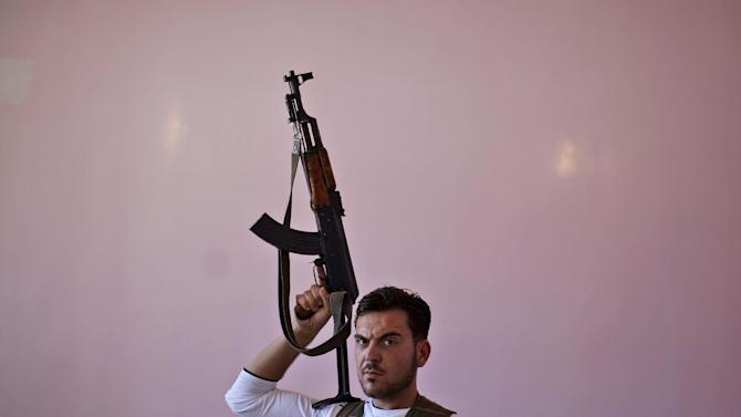 Syrian rebel fighter, Mohammed Sami, 22, a barber, poses for a picture after returning from fighting against Syrian army forces in Aleppo, at a rebel headquarters in Marea on the outskirts of Aleppo city, Syria, Sunday, Aug. 26, 2012. In their previous lives, they were butchers, barbers, construction workers and university students. Now they are rebels fighting a civil war they hope will end the regime of Syrian President Bashar Assad. (AP Photo/Muhammed Muheisen)