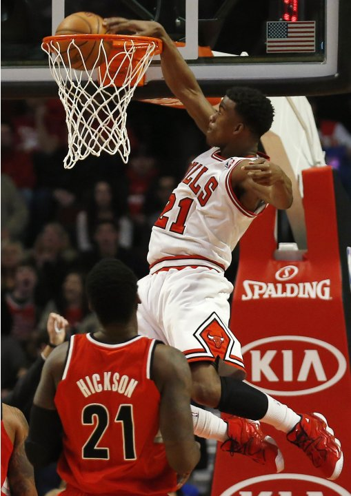 Chicago Bulls' Butler dunks the ball as Portland Trail Blazers' Hickson looks on during the first half of their NBA basketball game in Chicago, Illinois