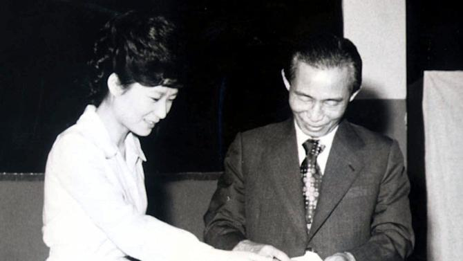 FILE - In this 1977 file photo, then South Korean President Park Chung-hee, right, and his daughter Park Geun-hye cast ballots in Seoul, South Korea. Park Geun-hye attempts to become the country's first female president and keep the government in conservative hands in the Dec. 19 election. She has been in the public eye longer than either of her rivals and is a skilled political operator, but she is also hounded by her late father's complicated legacy, which continues to divide many South Koreans. (AP Photo/Yonhap, File) KOREA OUT