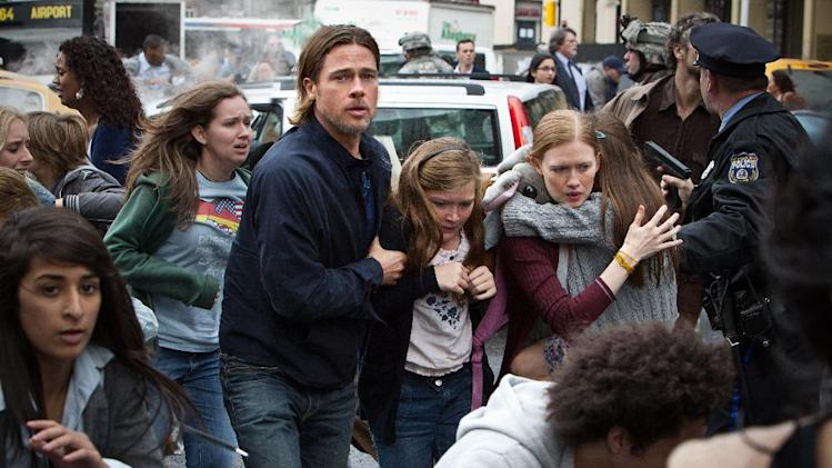 "This publicity image released by Paramount Pictures shows, from center left, Brad Pitt as Gerry Lane, Abigail Hargrove as Rachel Lane, and Mireille Enos as Karin Lanein a scene from ""World War Z."" In a small-scale marketing experiment, for $50, some fans got to see Brad Pitt's hotly anticipated zombie thriller ""World War Z"" before all their friends. They also got 3D glasses to keep, popcorn, a poster, and a promised copy of the DVD when it comes out. (AP Photo/Paramount Pictures, Jaap Buitendijk)"
