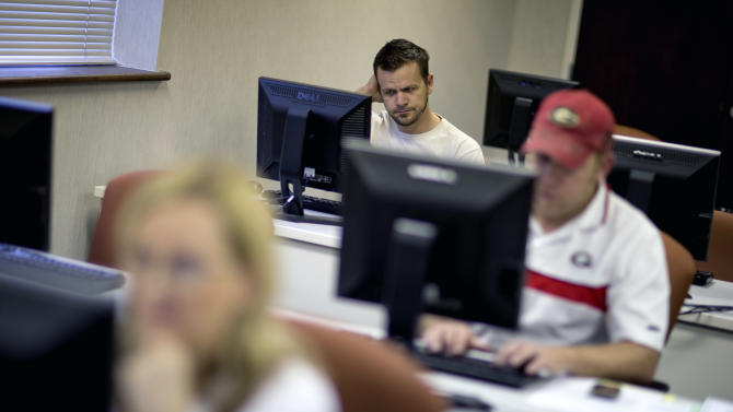 In this Aug. 22, 2012 file photo, Scott Marshall, top, of Calhoun, Ga., files for unemployment, in Dalton, Ga. Fewer Americans applied for unemployment benefits last week, and a private survey showed businesses stepped up hiring in August. The data sketched a brighter outlook for the job market one day before the government reports on August employment. (AP Photo/David Goldman, File)