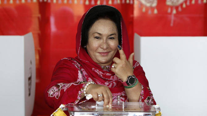 Rosmah Mansor, wife of Malaysian Prime Minister Najib Razak, shows photographers her finger marked with indelible ink while casting her ballot in the general elections at a polling station in Pekan, Pahang state, Malaysia, Sunday, May 5, 2013. Malaysians have begun voting in emotionally charged national elections that could see the long-ruling coalition ousted after nearly 56 years in power. (AP Photo/Lai Seng Sin)