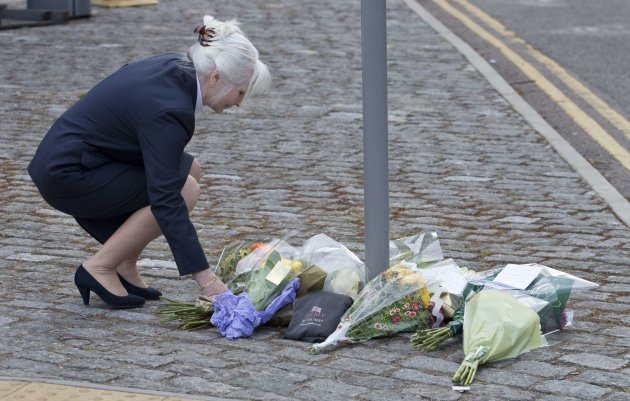 A woman places flowers outside the Royal Military Barracks, near the scene where a British soldier was killed in Woolwich, southeast London