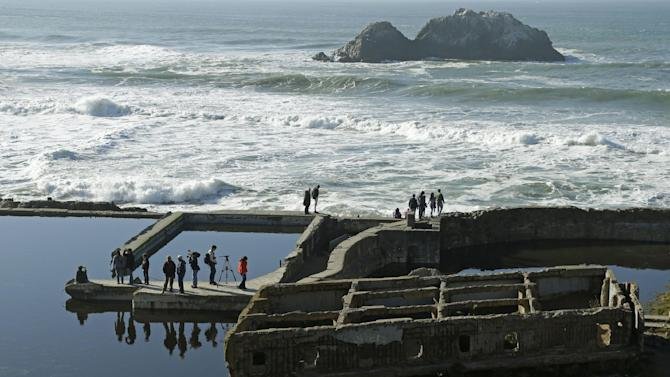 Spectators line the ruins of the Sutro Baths for a glimpse of a river otter Thursday, Jan. 3, 2013, in San Francisco. For the first time in decades, a river otter has made San Francisco its home, taking up residence in the ruins of a 19th century seaside public pool facing the Pacific Ocean. (AP Photo/Ben Margot)