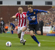 Stoke City's Dean Whitehead, left, in action with Manchester United's Phil Jones during their English Premier League soccer match at the Britannia Stadium, Stoke, England, Saturday Sept. 24, 2011. (AP Photo/Jon Super)