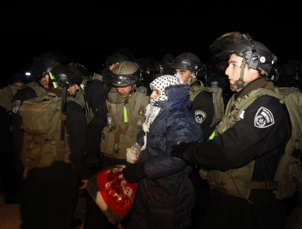 Israeli border police evict a Palestinian activist from an area known as E-1 near Jerusalem, Sunday, Jan 13, 2013. Palestinian activists erected tents in the area on Friday saying they wanted to &quot;establish facts on the ground&quot; to stop Israeli construction in the West Bank. The Palestinian activists were borrowing a phrase and a tactic, usually associated with Jewish settlers, who believe establishing communities means the territory will remain theirs once structures are built. (AP Photo/Nasser Shiyoukhi)