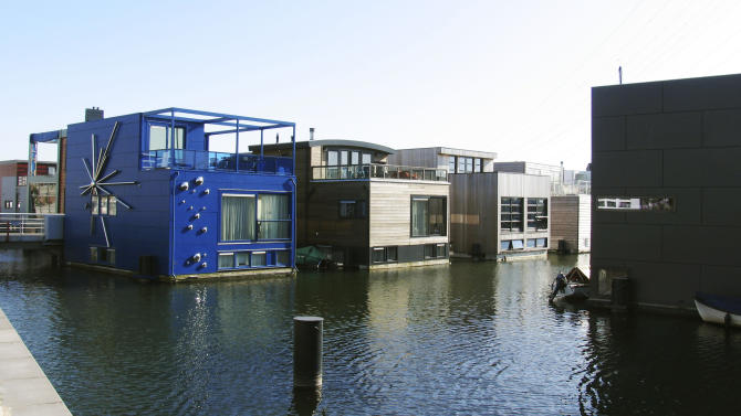 FILE - In this Wednesday, March 28, 2012 file photo, amphibious homes float on the harbor in the IJburg neighborhood in Amsterdam. IJburg is a new district in the eastern part of town completely surrounded by water. The Netherlands, a third of which lies below sea level, has been managing water since the Middle Ages. (AP Photo/Margriet Faber)