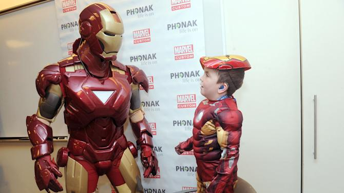 IMAGE DISTRIBUTED FOR PHONAK - Phonak hearing aid wearer Anthony Smith, 5, of Salem, NH, shares a moment with Marvel's Iron Man, Tuesday, Feb. 26, 2013, in New York, during an event announcing a unique partnership between Phonak and Marvel Custom Solutions to produce an educational poster geared for children that highlights the benefits of hearing aids. (Photo by Diane Bondareff/Invision for Phonak/AP Images)