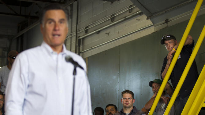 Employees Middlesex Truck and Coach look on as Republican presidential candidate, former Massachusetts Gov. Mitt Romney makes a statement on jobs during a campaign on Thursday, July 19, 2012 in Roxbury, Mass.  (AP Photo/Evan Vucci)