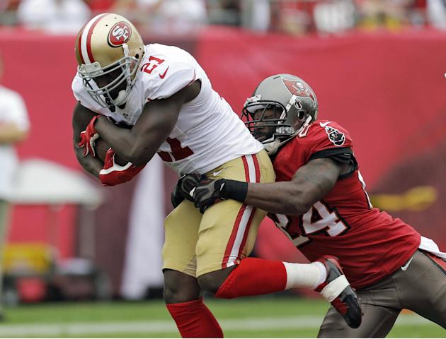 FILE - In this Dec. 15, 2013, file photo, San Francisco 49ers running back Frank Gore (21) is grabbed by Tampa Bay Buccaneers cornerback Darrelle Revis (24) during the first quarter of an NFL football
