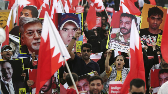 "Bahrainis, some of them waving flags, chant anti-government slogans and hold up signs urging freedom for jailed doctors, political leaders and others during a march in Jidhafs, Bahrain, Saturday, Aug. 23, 2014. The sign at back second right reads, ""free blind prisoner Jaffar Matooq for treatment."" A small group of youths began blocking streets to challenge riot police after the march by opposition groups accusing the government of naturalizing tens of thousands of people, largely to work in the police and military, in an effort to change the tiny Gulf island monarchy's demographics. (AP Photo/Hasan Jamali)"