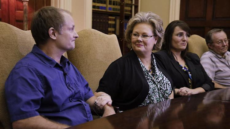 Teresa Russell, second from left, comforts her brother, Jeffrey Russell, left, as Jeffrey talks about their mother, Janet Russell, on Friday, Oct. 5, 2012, in Nashville, Tenn.  Janet Russell is suffering from a deadly fungal meningitis that 39 people in six states have also contracted after getting steroid shots for back pain. Five have died. Sister Tracy Barreiro, is seated second from right, and father Bobby Russell, is at right. (AP Photo/Mark Humphrey)
