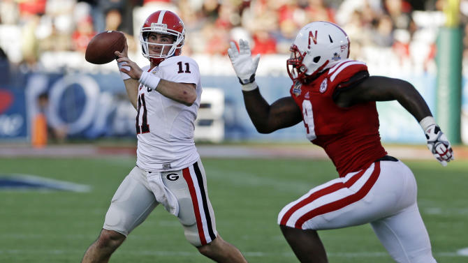 Georgia quarterback Aaron Murray (11) throws a pass as he is pressured by Nebraska defensive end Jason Ankrah (9) during the second half of the Capital One Bowl NCAA college football game, Tuesday, Jan. 1, 2013, in Orlando, Fla. Georgia won 45-31. (AP Photo/John Raoux)