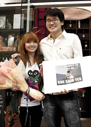 In this Nov. 30, 2011 photo provided by Crazy Monkey Studio, Malaysian Timothy Tiah, 27, poses with his girlfriend Audrey Ooi, 26, after proposing to Ooi at an Italian restaurant in Kuala Lumpur, Malaysia. An emotional video of Tiah propose to his girlfriend turned Tiah and his now-fiancee into unexpected role models for numerous young romantics worldwide. (AP Photo/Crazy Monkey Studio, Geh Chee Wooi) EDITORIAL USE ONLY, NO SALES