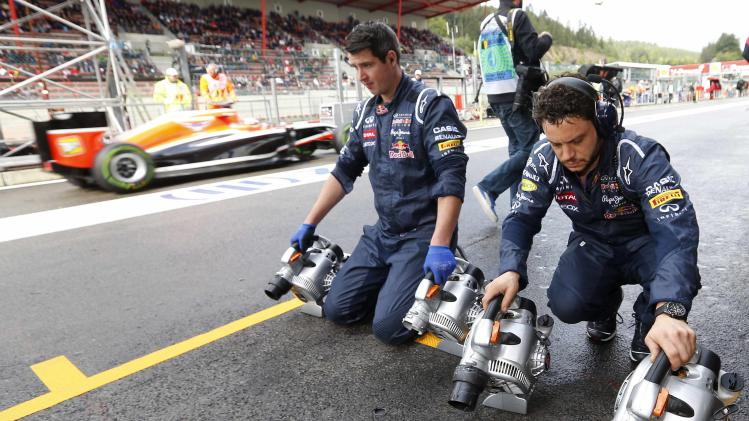 Technicians of Red Bull Racing Formula One team dry the track in the pitlane during a practice session at the Belgian F1 Grand Prix in Spa Francorchamps