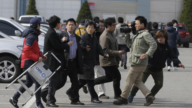 Journalists ask a worker, third from left, who arrived back from North Korea's Kaesong at the customs, immigration and quarantine office near the border village of Panmunjom, that has separated the two Koreas since the Korean War, in Paju, north of Seoul, South Korea, Thursday, April 11, 2013. Bracing for what South Korea's foreign minister warned could be a test-fire of a medium-range missile, Seoul deployed three naval destroyers, an early warning surveillance aircraft and a land-based radar system, a Defense Ministry official said in Seoul. (AP Photo/Lee Jin-man)