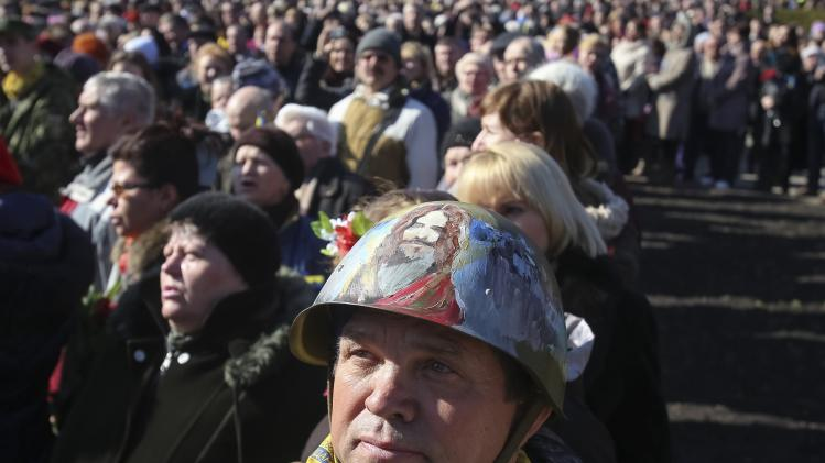 People take part in a rally to mark the 200th birthday of Ukrainian poet Taras Shevchenko near a monument of him in central Kiev